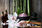 Spa set on mirror surface on wooden wall background