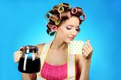 Beautiful girl in hair curlers on blue background