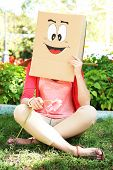 Woman with cardboard box on her head with happy face, holding flower, outdoors