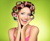 Beautiful girl in hair curlers on green background