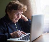 Old woman typing on laptop keyboard.