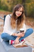 Young beautiful girl sitting on a bench in a park