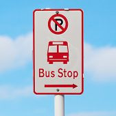 The Sign Shows Way To Bus Stop And No Parking Area With Blurry Blue Sky Background.