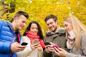 season, people, technology and friendship concept - group of smiling friends with smartphones in autumn park