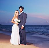 Beautiful Wedding Couple, Bride and Groom on the Beach at Sunset