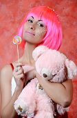woman laughing with candy and beautiful make-up  whith taddy bear