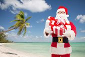 christmas, holidays, travel and people concept - man in costume of santa claus with gift boxes over tropical beach background