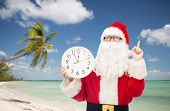 christmas, holidays, travel and people concept - man in costume of santa claus with clock showing twelve pointing finger up over tropical beach background