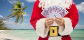 christmas holidays, winning, currency, travel and people concept - close up of santa claus with euro money over tropical beach background