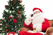 holidays, technology and people concept - man in costume of santa claus with smartphone, presents and christmas tree