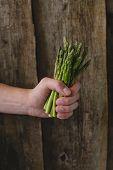 Man holding delicious, fresh asparagus