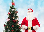 holidays and people concept concept - man in costume of santa claus with christmas tree over blue lights background