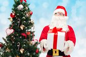 christmas, holidays and people concept - man in costume of santa claus with gift box and tree over blue lights background