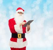 christmas, holidays, technology and people concept - man in costume of santa claus with tablet pc computer over blue lights background