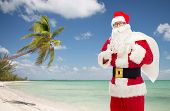 christmas, holidays, gesture, travel and people concept - man in costume of santa claus with bag showing thumbs up over tropical beach background