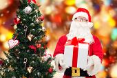 christmas, holidays and people concept - man in costume of santa claus with gift box and tree over red lights background