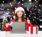 christmas, holidays, technology and shopping concept - smiling woman in santa helper hat with credit card, gift box and laptop computer showing thumbs up gesture over snowy night city background
