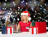 christmas, holidays, technology and shopping concept - smiling woman in santa helper hat with gifts, credit card and laptop computer over blue snowy background