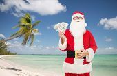 christmas holidays, winning, currency, travel and people concept - man in costume of santa claus with dollar money over tropical beach background
