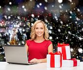 christmas, holidays, technology, advertising and people concept - smiling woman in red blank shirt with gifts and laptop computer over snowy night city background