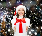christmas, winter, happiness, holidays and people concept - smiling woman in santa helper hat with gift box over snowy city background