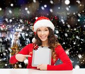 christmas, holidays, technology and people concept - smiling woman in santa helper hat with tablet pc computer over snowy night city background