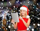 christmas, technology, present and people concept - smiling woman in santa helper hat with tablet pc computer over snowy night city background