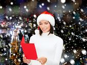 christmas, holidays, celebration, greeting and people concept - smiling woman in santa helper hat with greeting card over snowy night city background