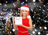 sale, gifts, christmas, holidays and people concept - smiling woman in red dress and santa helper hat with white blank shopping bag over snowy night city background