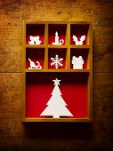 Christmas decoration, hand cut paper craft in a wooden printer tray, on a old wooden wall. .