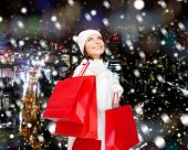 happiness, winter holidays, christmas and people concept - smiling young woman in white hat and mittens with red shopping bags over snowy city night background