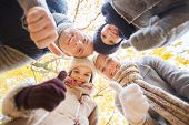 family, childhood, season, gesture and people concept - happy family showing thumbs up in autumn park