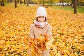 childhood, season and people concept - smiling little girl holding autumn leaves in park