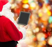 christmas, advertisement, technology, and people concept - man in costume of santa claus with tablet pc computer over red lights background