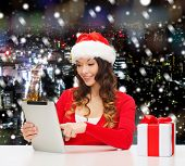 christmas, holidays, technology and people concept - smiling woman in santa helper hat with gift box and tablet pc computer over snowy night city background