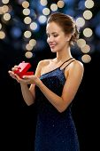 holidays, presents, luxury and happiness concept - smiling woman in dress holding red gift box night lights background