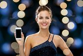 technology, communication, holidays, advertising and people concept - smiling woman in evening dress holding smartphone over night lights background