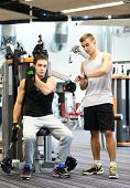 sport, fitness, equipment, lifestyle and people concept - men exercising on gym machine