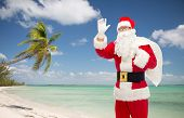 christmas, holidays, gesture, travel and people concept - man in costume of santa claus with bag waving hand over tropical beach background
