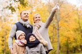 family, childhood, season, gesture and people concept - happy family pointing finger in autumn park