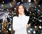 clothing, winter holidays, christmas and people concept - smiling young woman iin white sweater over snowy night city background