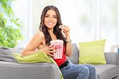 Young woman eating popcorn seated on sofa at home