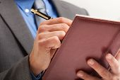 Detail of a businessman writing on his agenda