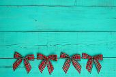 Blank antique green distressed wooden wall with red plaid bow border