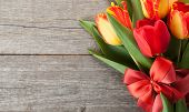 Fresh colorful tulips bouquet with ribbon and bow over wooden background with copy space