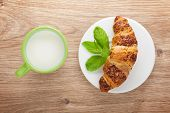 Milk and fresh croissant on wooden table