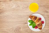 Orange juice and fresh croissant with berries on wooden table background with copy space