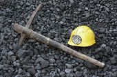 stock photo of mines  - Pickaxe mining helmet in the background heap of coal - JPG