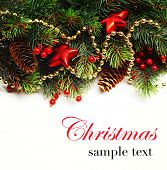 Christmas background. Christmas boarder with fir tree branch with cones and ornament. Christmas baubles in golden and red colour. Close up with copy space and sample text. Winter holidays concept.