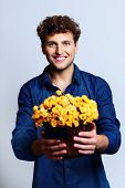 Happy man holding bucket with flowers